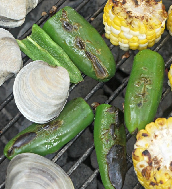 clams, jalapeño peppers, and corn cooking on the charcoal grill