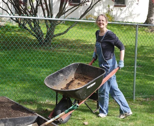woman in garden with wheelbarrow