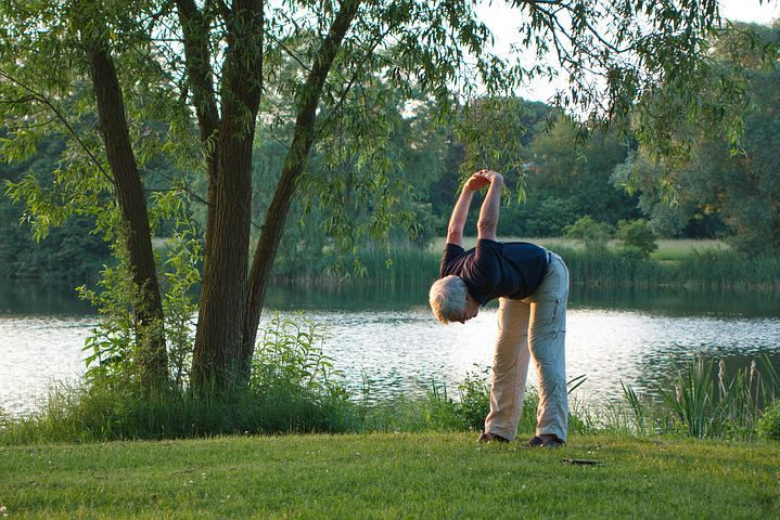 man stretching outdoors near a pond